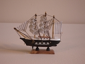 Small Souvenir Ship, Black W/White Pattern, W/Brown Bottom. L-6.25in  W-1.5in  H-6.25in