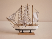 Medium Souvenir Ship W/White Sails W/Black Stripes, White W/Black Bottom & Gold Cannons.  L-9.5in  W-2.25in  H-9.5in