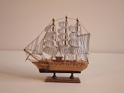 Medium Souvenir Ship W/White Sails & Black Stripes, Wood Brown W/Black Bottom & Gold Cannons.  L-9.5in  W-2.25in  H-9.5in