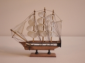 Medium Souvenir Ship W/White Sails, White W/Black Stripes, W/Wood Bottom & Gold Cannons.  L-9.5in  W-2.25in  H-9.5in